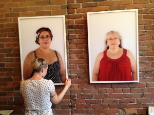 Toni Latour hanging photos in a gallery