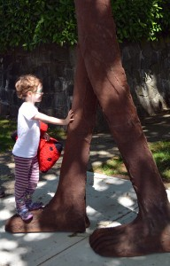 A child examines one of the Walking Figures
