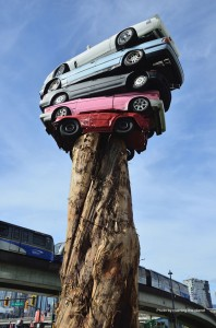 Cedar Tree with 5 full sized cars on top and a skytrain in the background