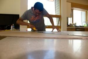 Rathin Barman scoring cardboard with a knife